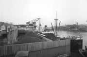 Bergen kullkompani. Forretningen ble grunnlagt 2/1 1880 av skipsreder S.M. Kuhnle. Firmaet var et handelsselskap som omsatte alle sorter brensel. Kullkranens lossekapasitet for kull var ca. 1000 à 1500 tonn per døgn Anlegget er her fotografert november 1929. Fotograf: Atelier KK. (Billedsamlingen UiB)
