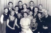 Foto: Aud foran i midten, sammen med mor, far og tolv av sine søsken. Ukjent fotograf, privat eie. Publisert med tillatelse fra Aud.