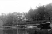 Villa Fredheim fotografert fra Store Lungegårdsvann i 1918. I forgrunnen skimtes Fjæreveien (Møllendalsveien) og i bakgrunnen Kronstad Hovedgård. Foto: Atelier KK. Billedsamlingen UiB. (Kat sign.: UBB-KK-N-176/004.)