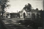 Haukeland hovedgård med portalen og vakten til Haukeland sykehus i forgrunnen. Bildet er tatt i 1912, ukjent fotograf. Fra arkivet etter Byggekomiteen for Haukeland sykehus.