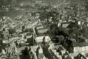 Flyfoto av Sydnesplassen. Johanneskirken sentralt i bildet, og Sydneshaugen skole til høyre. Foto fra 1950-tallet. Fotograf: Ukjent. Arkivet etter Reguleringsvesenet, Bergen Byarkiv.