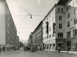 Olav Kyrres gate mot Småstrandgaten. Det tidligere hovedpostkontoret i Bergen til venstre, og Olav Kyrres gate nr. 1 til høyre.<br />Fotograf: Ukjent.<br />Arkivet etter Reguleringsvesenet, Bergen Byarkiv.