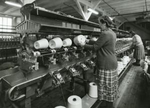 Arbeidere ved Salhus Tricotagefabrik holder orden på trådspoler. Udatert foto. Fotograf: Ukjent. Arkivet etter Salhus Tricotagefabrik A/S, Bergen Byarkiv.