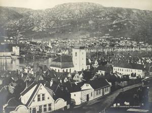 Utsikt fra Fredriksberg i 1865. Lav trehusbebyggelse domineres av Nykirken. Arkivet etter Bergen formannskap, Bergen Byarkiv.