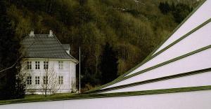 Landås hovedgård i skarp kontrast til det moderne kirkebygget i forgrunnen. Fotograf: Norvall Skreien.