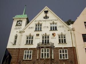 Selve symbolet på Hansaen i Bergen, Det norske kontors våpen (den kronede tørrfisk og halve Lübecks dobbeltørn), pryder fasaden av Kjøpmannsgården.