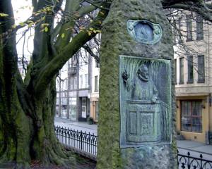 Petter Dass pryder den ene siden av dette minnesmerket, bergenske Dorothea Engelbretsdatter den andre. De to høyst ulike dikterne brevvekslet på rim, og det er en av grunnene til at de har fått en felles bauta, som nå er plassert syd for domkirken. Bronserelieffene på begge sider av støtten er utført av Ambrosia Tønnesen. Fotograf: Norvall Skreien.