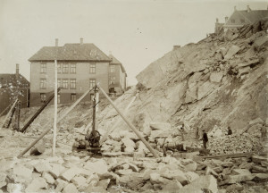 Stein til Bergens kaier ble brutt i Jektevikens steinbrudd ved Dragefjellet. I bakgrunnen til høyre ser en Dragefjellet skole. Udatert foto fra tidlig 1900-tall. Fotograf: Ukjent. Arkivet etter Havnekontor/havnefogd, Bergen Byarkiv.