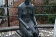 """Skulptur, """"Knelende kvinne"""" laget av billedhuggeren Hans Jacob Meyer (1907–93). Skulpturen er en replikk av krigsminnesmerket som ble reist av Haus kommune i 1952 utenfor Arna kirke. Fotograf: Olav Alexander Mjelde. Bergen Byarkiv."""