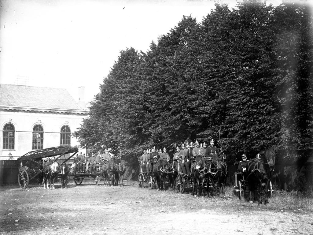 Oppstilling av brannvesenet på øvelsesplassen ved den gamle turnhallen, der jernbanestasjonen er i dag. Arkivet etter Bergen brannvesen, A-1181.