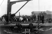 Havneingeniørens foto av arbeidere som jobber med en kai. Legg merke til dykkeren med utstyr. Udatert. Ukjent fotograf.